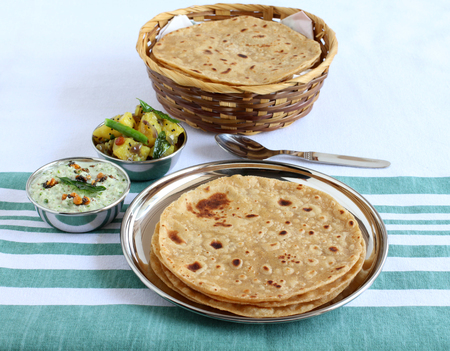 Chapati or Indian flat bread, which is a traditional and popular vegetarian breakfast or lunch item, with potato and onion curry and coconut chutney as side dishes, on a steel plate. Imagens