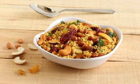Poha chivda, an Indian traditional, popular, delicious, and healthy vegetarian snack, is made from items like flattened rice, cashew nuts, peanuts, dry coconut, turmeric, and curry leaves. Imagens