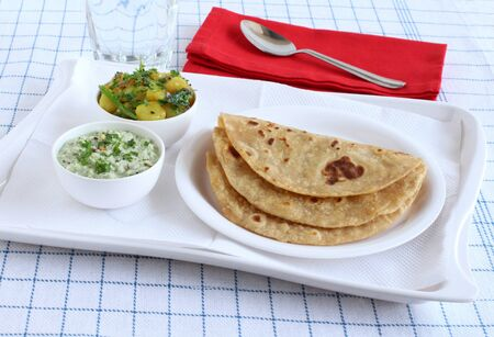 Chapati or Indian flat bread, which is a traditional and popular vegetarian breakfast or lunch item, with potato and onion curry and coconut chutney as side dishes, on a plate in a tray.