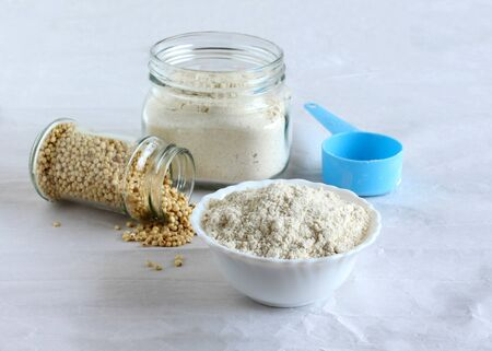 Sorghum flour, a healthy food and that is freshly ground, a whole grain and gluten free, in a ceramic bowl and jar, and sorghum spilled from a bottle, and a measuring cup. Imagens