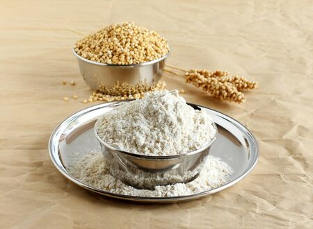 Sorghum flour, a healthy food and that is freshly ground, a whole grain and gluten free, in a steel bowl, and in the background is a bowl of sorghum and its stalk. Imagens