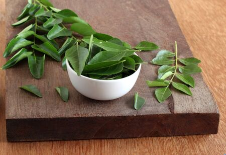 Curry leaves, which are a healthy ingredient used in tempering for Indian food like sambar, rasam and curries, and also as a flavoring agent, and their twigs, in a bowl.