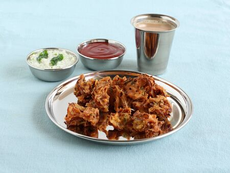 Pakoda, a traditional, popular, delicious, and an Indian vegetarian home-cooked snack, on a steel plate, with coconut chutney and ketchup as side dishes, and a cup of tea.