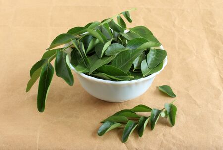 Curry leaves, which are a healthy ingredient used in Indian food like sambar, rasam and curries, and also as a flavoring agent, in a ceramic bowl.