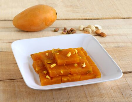 Mango halwa, a popular and delicious sweet dish, is made from ingredients like mango pulp, sugar, cashew nuts, almonds, and ghee, on a tray on a wooden background.