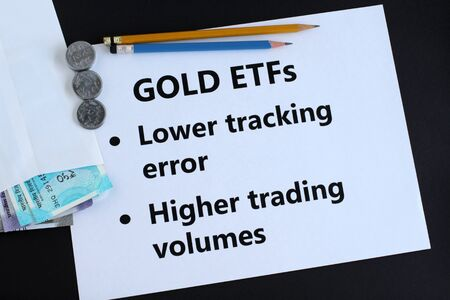 Gold exchange traded funds, or ETFs, an investment in Indian rupees concept, highlighting two of the key buying traits, and Indian rupees in an envelope.