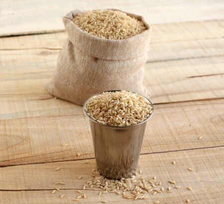Brown rice, which is a whole grain and a healthy food, in a steel cup, and in the background is a sack of brown rice, on a wooden background.