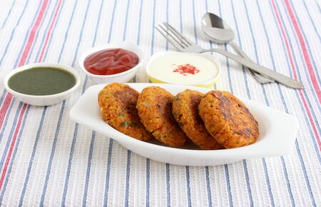 Kabuli chana tikkis, or chickpea patties, a healthy, vegetarian, delicious, and Indian food, with green chutney, ketchup, and curd with a topping of chili powder.
