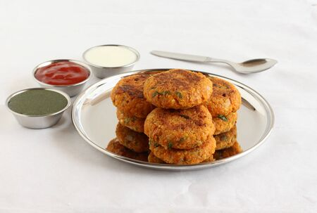 Kabuli chana tikkis, or chickpea patties, a healthy, vegetarian, delicious, and Indian food, with green chutney, ketchup, and curd, stacked on a steel plate. Stock Photo