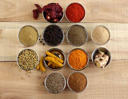 Kolendra, papryka, czerwone chili, imbir, kurkuma i kminek, indyjskie przyprawy i ich proszki, które są zdrowymi składnikami do aromatyzowania potraw, w stalowych miseczkach na drewnianym tle. Zdjęcie Seryjne