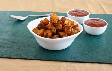 Crispy potato fry, or aloo fry, an Indian vegetarian snack and a side dish for items like chapati, and ketchup in bowls. Stock Photo