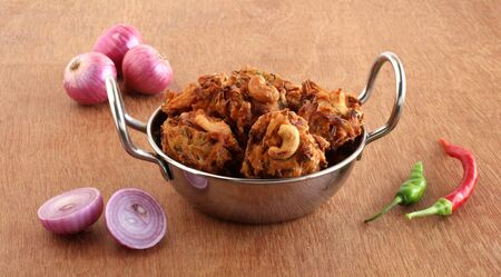 Pakoda, or pakora, a traditional, popular, and vegetarian Indian snack and side dish, with onion as the main ingredient, in a steel wok on a wooden background.