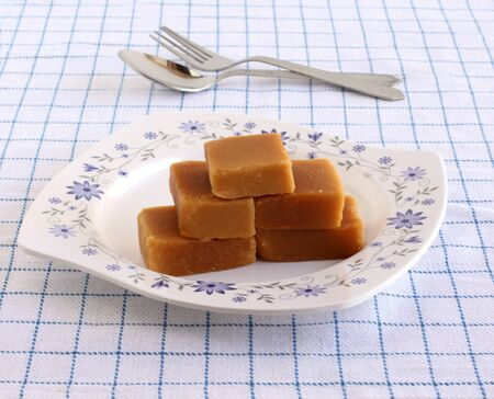 Mysore pak, a traditional, popular, and delicious sweet dish native to the city of Mysore, Karnataka, India, stacked on a ceramic plate and steel fork and spoon. Stock Photo
