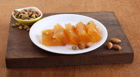 Bombay halwa, a popular Indian sweet dish is made from ghee and corn flour and has ingredients like almonds, cashew nuts, and pistachios, on a plate on a wooden board.