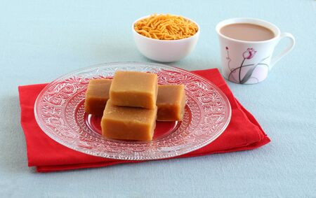 Mysore pak, a traditional, popular, and delicious sweet dish native to the city of Mysore, Karnataka, India, on a glass plate with tea and bhujia, which is a snack.