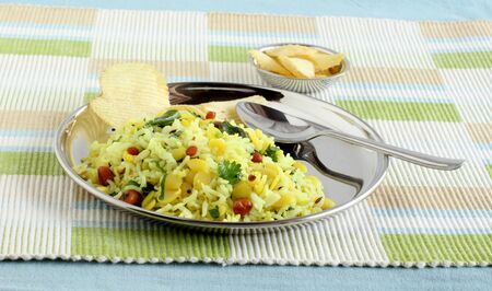 Lemon rice, a traditional, popular, Indian, and vegetarian dish, on a steel plate, and potato chips as a side dish. Stock Photo
