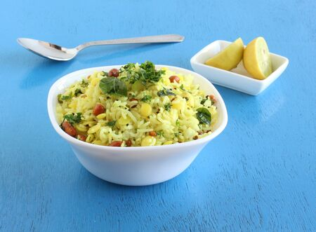 Lemon rice, a traditional, popular, delicious and south Indian vegetarian dish, in a bowl, and sliced lemons. Stock Photo