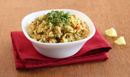 Pongal, a traditional, popular, delicious, and south Indian vegetarian rice dish, in a bowl on a red napkin, and lemon pieces. Stock Photo