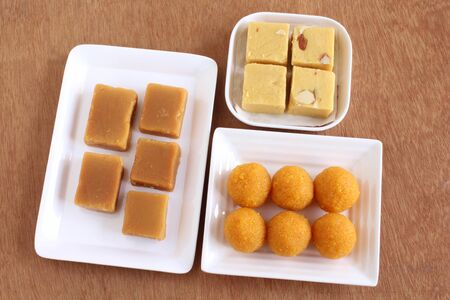 Mysore pak, soan papdi, and laddu, three of the traditional and popular Indian sweet dishes, on ceramic plates on a wooden background.