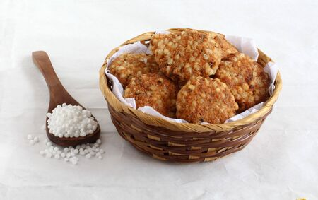 Sabudana vada, made from sago, is a traditional, popular, delicious, and vegetarian snack, native to Maharashtra, India, in a basket, and sago on a wooden spoon. Stock Photo