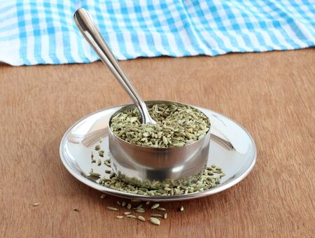 Fennel seeds, or soumph, a healthy food, are said to aid digestion and work as a mouth freshener, in a steel bowl with a spoon on a steel plate.