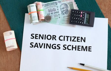 Senior citizen savings scheme, a low-risk investment option, concept highlighted through text on paper, Indian rupees and coins, and a pencil and pen on a wooden background.