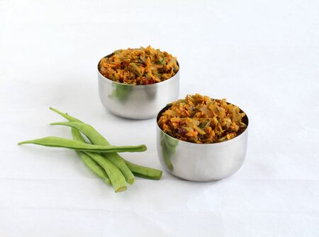 Cluster beans curry, also known as gawar ki sabzi, is a healthy, Indian, and vegetarian side dish for items like chapathi and roti, in steel bowls. Stock Photo