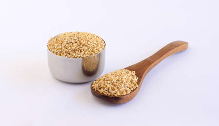 Steel-cut gluten free oats, which are in the category of whole grains, a healthy food, on a wooden spoon and in a steel bowl.