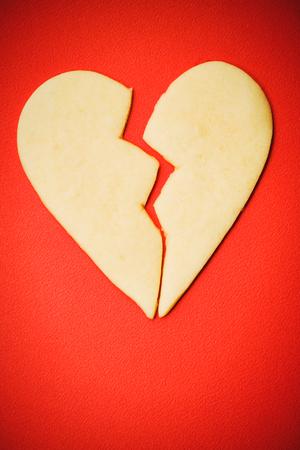 dissappointed: Broken heart Valentines Day sugar cookie on red background