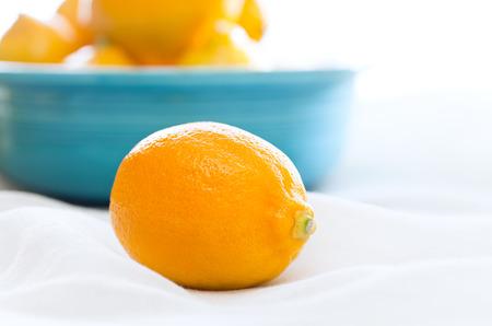 lemony: Bowl of lemons, one up close, in a bright daylight setting.