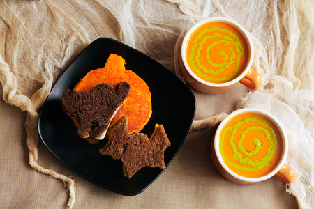 Rye, pumpernickel and ornage colored cut-out Halloween grilled cheese sandwiches. Tomato soup with pesto swirls in vintage orange cups. Shredded stained gauzy background for effect.