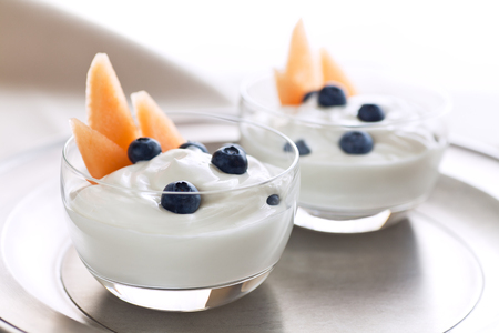 Cantaloupe: Greek-style plain yogurt with blueberries and cantaloupe on pewter plate. Serving for two.