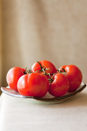 lycopene: Ripe tomatoes still on the vine in natural light setting.