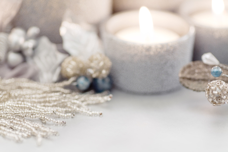 intentional: Intentional blur to create holiday background. Silver Christmas themed candles and glass beads. Focus on the strand of glass beads. Room for copy space.