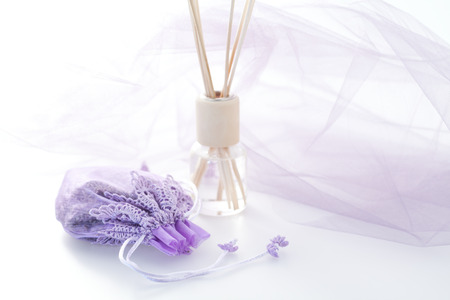 lavender coloured: Lavender flowers in pretty sachet, scented reed diffuser, matching purple colored netting in backround.