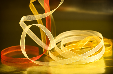 shimmery: Multicolored shimmery ribbon against a golden reflective surface creates a festive holiday theme.