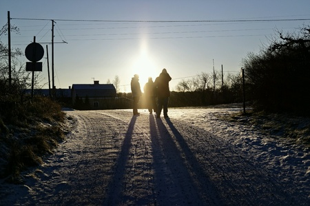 backlights: Three people talking on a road in a winter landscape Stock Photo