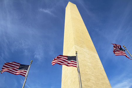 Washington Monument in Washington DC with flapping american flag on flagpoles photo