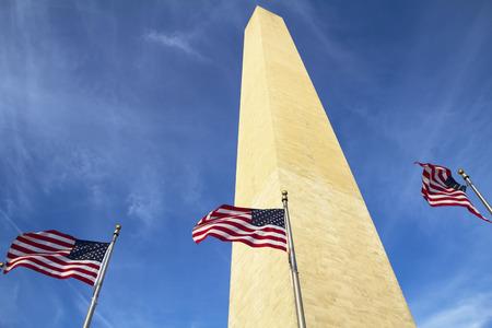 flagpoles: Washington Monument in Washington DC with flapping american flag on flagpoles