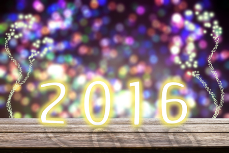 table top: Happy new year wood table top on 2016 and blur bokeh background with fireworks colorful Stock Photo