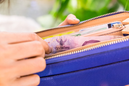wasteful: Hand woman picking bill five hundred in blue wallet