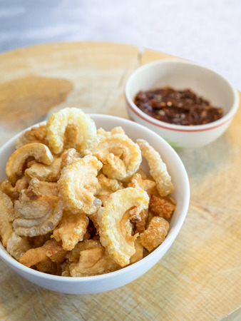 chicharon: Pork snack, pork rind in bowl with thai chili sauce on wood block