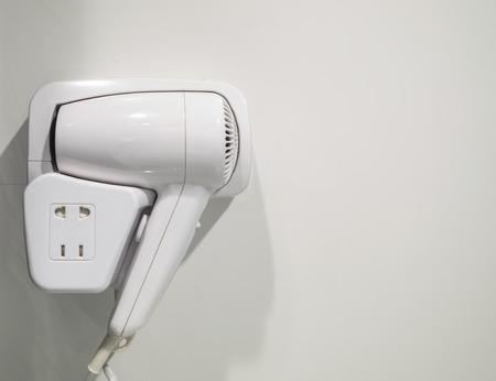 bathroom wall: Hair dryer hanging on wall in bathroom