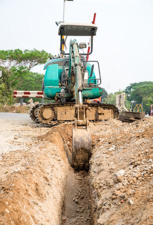 dredging: Green backhoe dredging soil earth