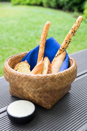 Bread loaf food snack in basket with blue napkin and white sauce at morning