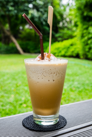 Coffee cappuccino churn froth in glass and straw on table Stock Photo