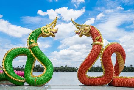 Statue naga mythology green red facing curve and blue sky in watsaman temple