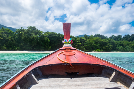 Front wooden longtail boat and crystal sea with blue sky