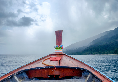 Longtail wooden boat traveling in storm blue sea Stock Photo