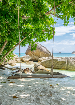 Wooden swing on white sand shady at lipe island Stock Photo